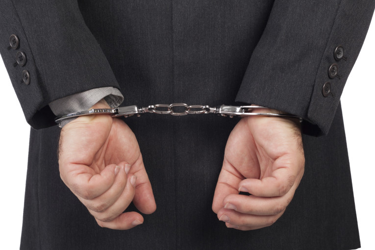 business man with a black suit in handcuffs